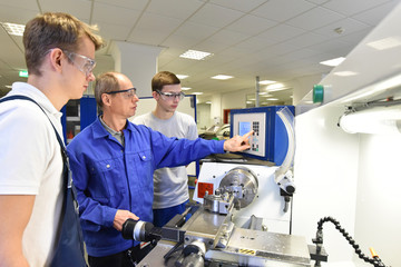 Azubis und Lehrer in der technischen Berufsausbildung stehen an einer Drehmaschine