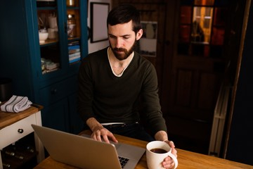 Handsome hipster using laptop in kitchen