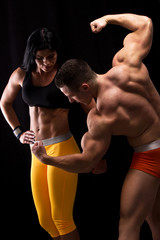 Strong man and a woman posing