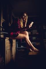 Pretty woman using smartphone in the dark