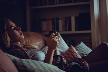 Pretty woman playing video games on sofa
