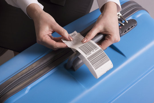 Airline check in luggage tag being attached to a suitcase