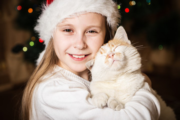 Cute little girl hugging her cat in Christmas