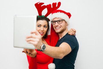 Young couple taking selfie using tablet pc. Christmas time.