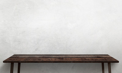 Modern wooden table with legs and free space. Cracked white wall texture in background.
