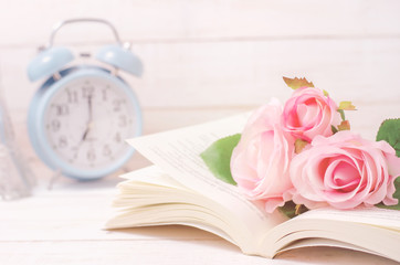 Pastel artificial rose and open book with vintage tone
