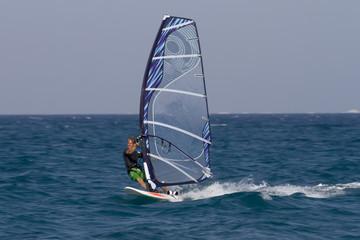 Windsurfen in Ägypten, Hurghada. Mann surft im Meer mit blauem Segel.