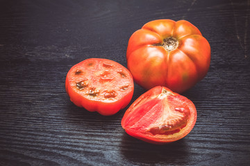 Fresh ripe tomatoes on a black table or board like background. T