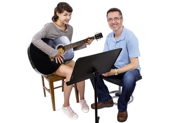 Music teacher tutoring young female student how to play guitar