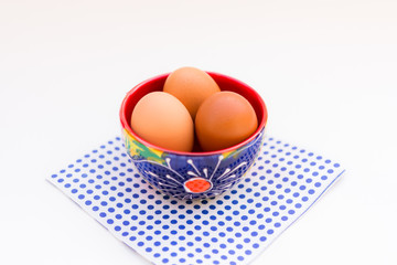 Aerial view brown eggs in colorful ceramic bowl isolated on table