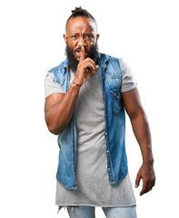 black man doing a silence sign