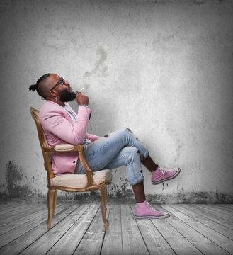 cool black man sitting on a sofa smoking