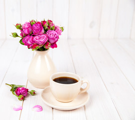 fresh flowers roses with a cup of coffee on white wooden background