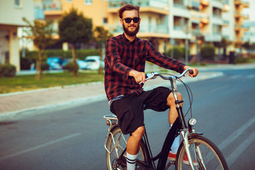 Man in sunglasses riding a bike on city street