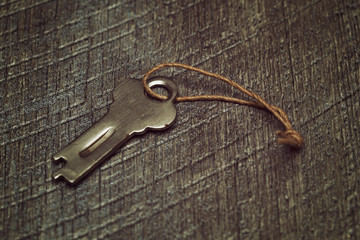 Vintage key on a wooden textured background