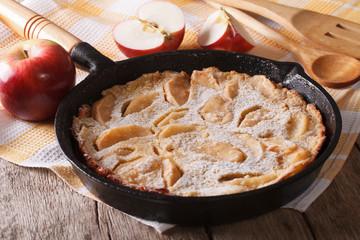Dutch baby pancake with apples in a pan closeup. Horizontal