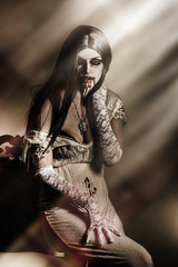 Gothic vampire under window moonlight at halloween
