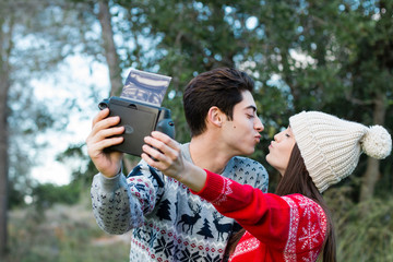 Young couple giving a kiss while make a photo with polaroid came