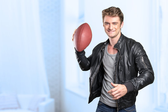 Young man football player portrait holding american football