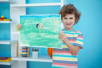 Smiling boy holding a picture