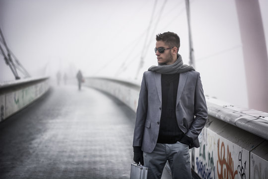 Handsome trendy man walking on a bridge in winter