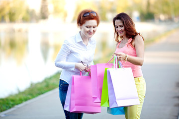 Two beautiful happy girls with colorful shopping bags in their hands on a walk in the afternoon. The concept of shopping