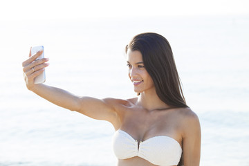 Girl taking fun selfie picture on beach vacation