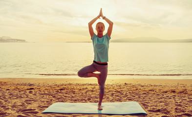 Girl in yoga pose of tree on beach