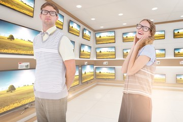 Composite image of geeky hipster couple looking at camera