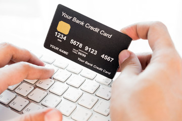 hand holding a credit card and typing. On-line shopping on the i