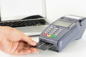 Hand Swiping Credit Card With Laptop In Background
