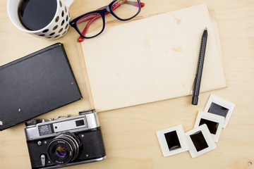 Old camera,cup of coffee, eyeglasses, blank note, pen and transparency slides