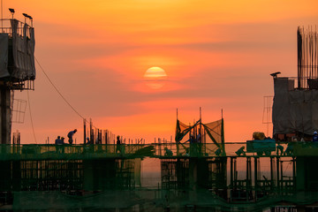 evening time of high building construction site, over time worke