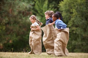 Gruppe Kinder beim Sackhüpfen