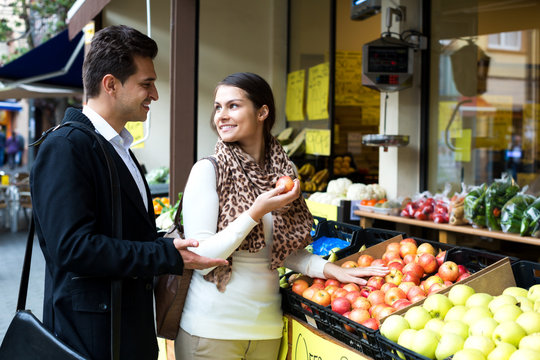 Young spouses choosing sweet fruits