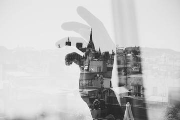 Double exposure with Barcelona and hand near the window