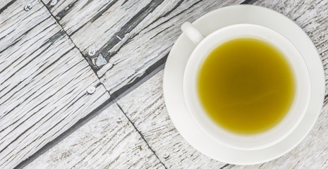 Japanese green tea in white cup over wooden background