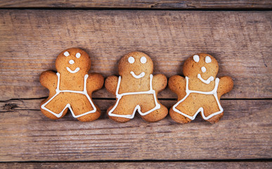 HIgh angle view of three gingerbread men on a rustic white kitchen table. The cookies are  plain and without icing.