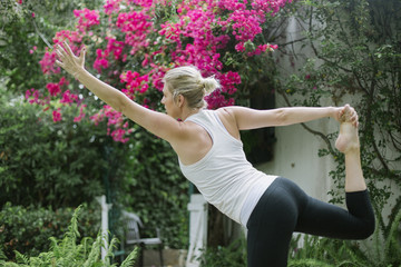 Blond woman doing yoga in a garden.