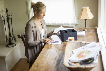 Blond woman sitting at a desk by a window, looking at  photographs.
