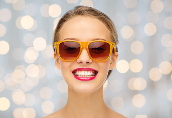 happy young woman in sunglasses with pink lipstick