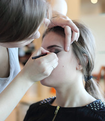 Closeup of a makeup artist applying makeup