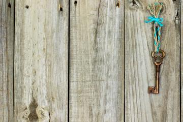 Bronze skeleton key hanging from rope on antique rustic wood door