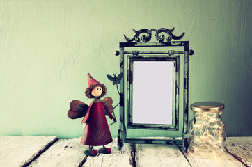 low key image of old victorian steel blue blank frame, mason jar with fairy lights and cute fairy on wooden table. vintage filtered image