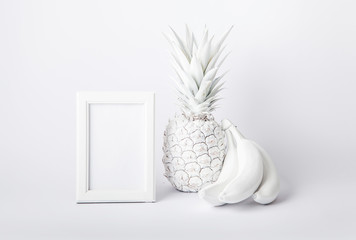 White frame with pineapple and bananas on a white background