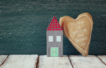 image of vintage wooden colorful house and fabric heart on wooden table in front of blackboard