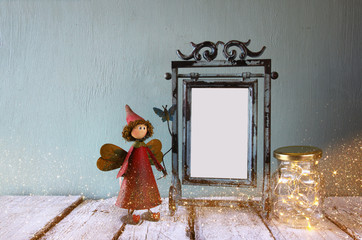 low key image of old victorian steel blue blank frame, mason jar with fairy lights and cute fairy on wooden table. vintage filtered image with glitter overlay
