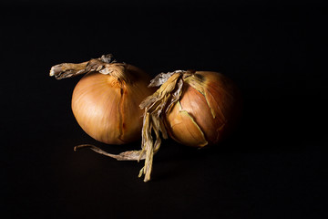 Two onions side by side on a studio shot with black background