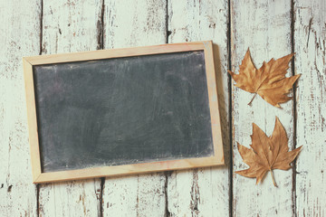 top view image of autumn leaves next to chalkboard over wooden textured background. copy space