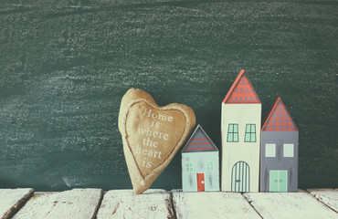 image of vintage wooden colorful houses and fabric heart on wooden table in front of blackboard